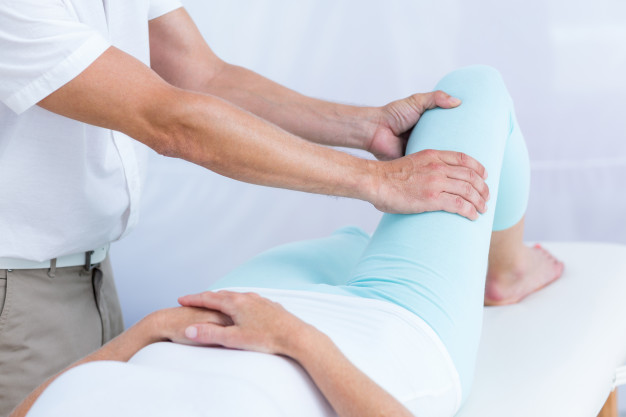 Physiotherapist doing leg massage to his patient Premium Photo