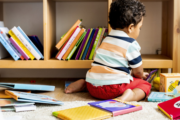 Little boy reading a book at library Premium Photo