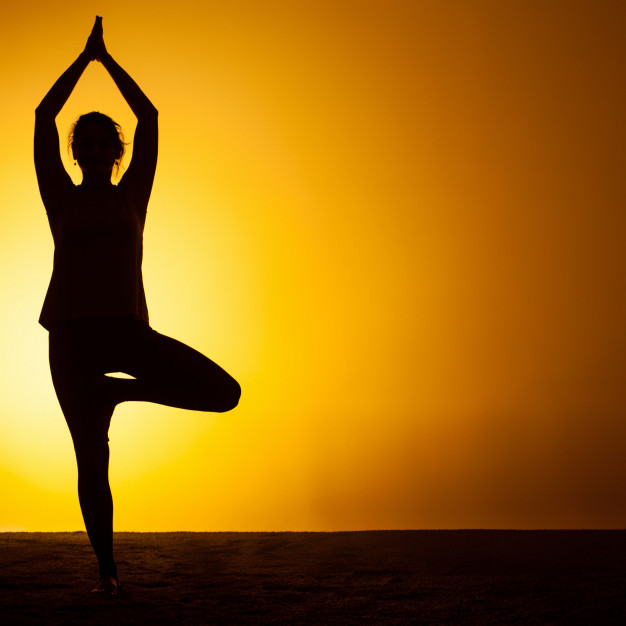 Woman practicing yoga in the sunset light Free Photo