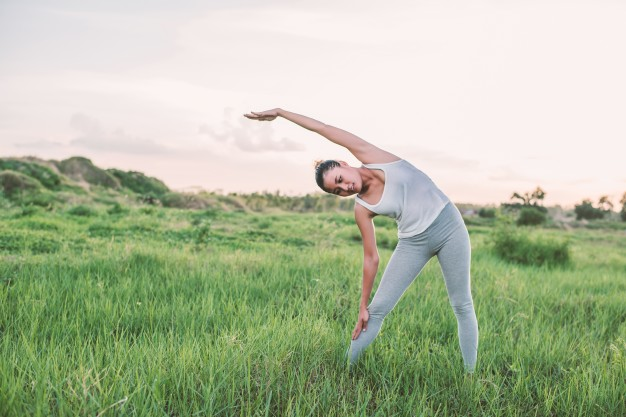 Active woman exercising in the meadow Free Photo