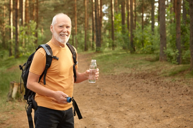 Cheerful attractive senior man with backpack hiking outdoors, smiling joyfully satisfying his thirst, holding bottle with drinking water, posing in pine forest. age, maturity and active lifestyle Free Photo